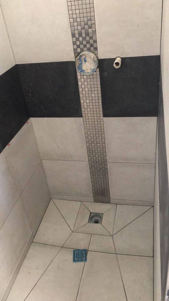 Duschkabine mit Fliesen und Zierstreifen